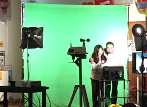 Students standing in front of a green screen