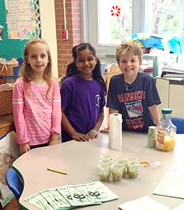 Three students pose with orange juice
