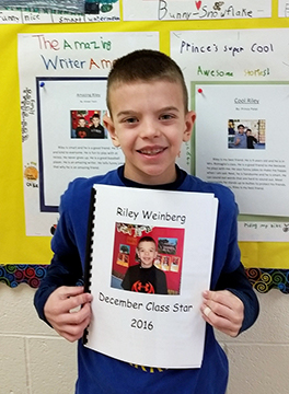 Riley Weinberg poses with a notebook reading Riley Weinberg December Class Star 2016