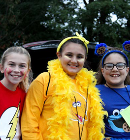 Three students dress up as Sesame Street and superhero characters