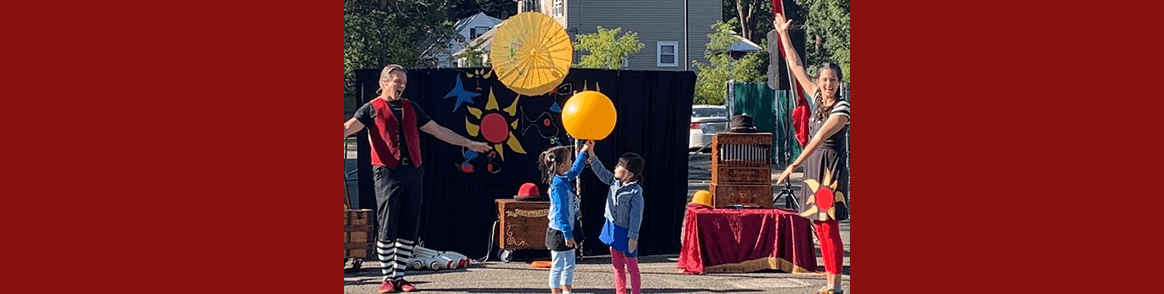 Two students participate in a circus activity with a balloon