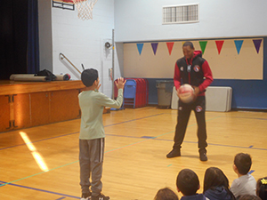 Basketball player passing a basketball to a student