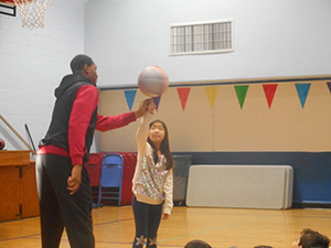 Basketball player showing a student how to spin the basketball on their finger
