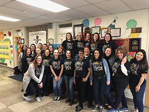 Staff members pose in their Autism Awareness t-shirts