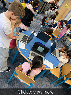 Students practice using Chromebooks at a table