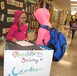 Two students stand near a desk with a sign reading Problem Solving Center