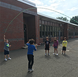 Students play with a large jump rope outside