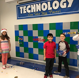 Group of students pose in front of a lego wall with a sign reading Technology Can Take You Places