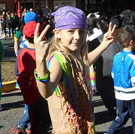 Student wearing a bandana and holding up peace signs with both hands walks