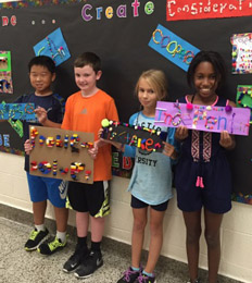 Four students pose together with art projects