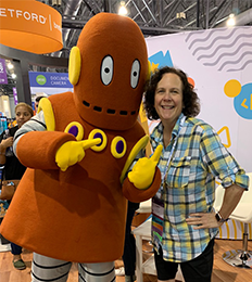 Female staff member poses with Brain Pop character Moby