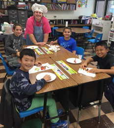 Students participate in a food activity with a staff member in a chef hat