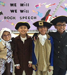 Four happy students wearing pilgrim outfits