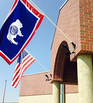 USA and Wyoming State flag on school building