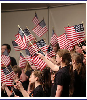 Group of students waving American flags in the air