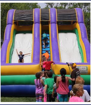 Students sliding down a bouncy slide