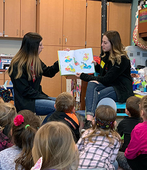 Two women reading to a group of students