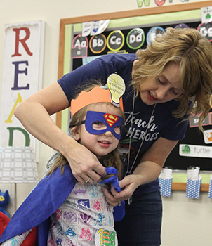 Staff member helping a student wearing a superhero outfit with her cape