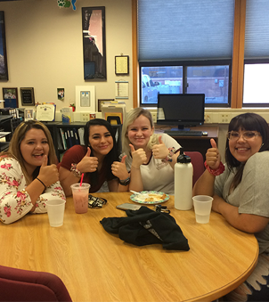 four staff members sitting at a table giving a thumbs up