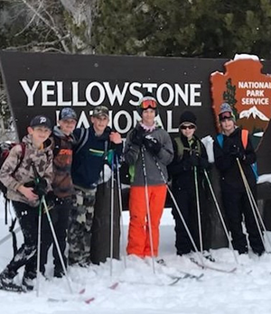 Students posing with ski equipment in front of a Yellowstone National Park sign