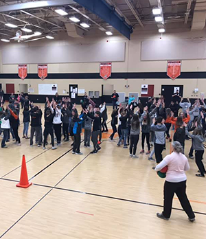 Students participating in a group activity and forming circles with their hands together in the gym