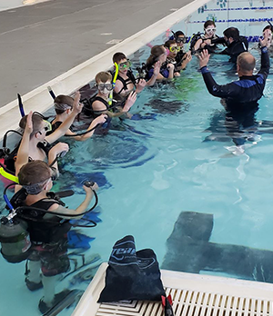 Students participating in a scuba activity in a pool with a scuba instructor