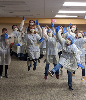 Students jumping in the air dressed in personal protective equipment