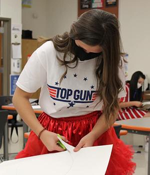 Female student cutting paper