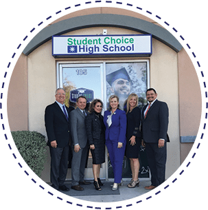 Staff members posing together in front of a Student Choice High School sign