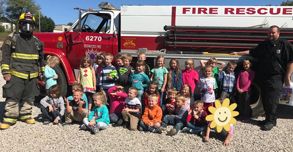students in front of a fire truck