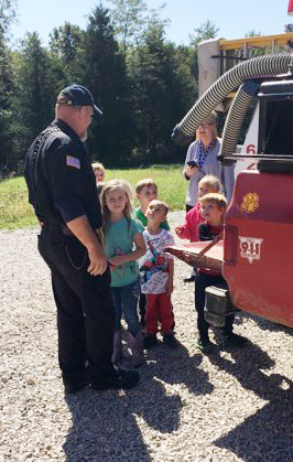 students talking to a fireman