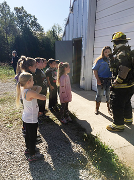 group of students talking to a fireman