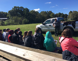 group of students listening to a fireman speak