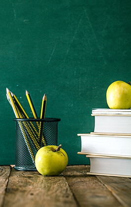 Apples, pencils, books and a blackboard