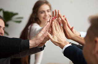 Group of motivated business people giving each other a high five