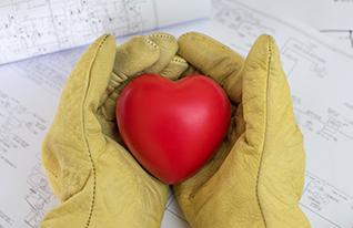 Maintenance worker hands in work gloves holding a heart