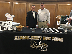 Dr. Scott A Deetz and a staff member pose in front of a Madison-Grant High School table