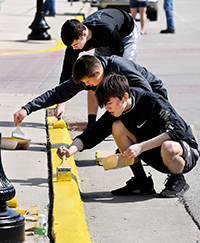 Three male students paint curbs