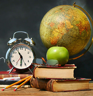 An apple, clock, globe, glasses, stacked books and pencils sit on a table in front of a blackboard