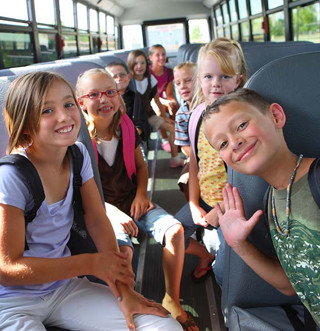 Students pose on a school bus