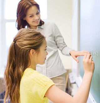 Female student writes on a blackboard as a teacher watches