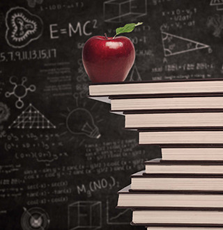Apple sitting on top of a stack of books in front of a blackboard