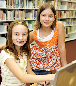 Two female students pose together in a library
