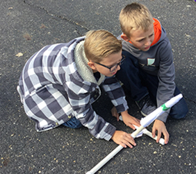 Twos students shooting off a rocket
