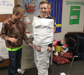 students wrapping a boy in toilet paper