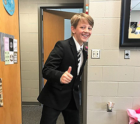Student wearing formal attire gives a thumbs up