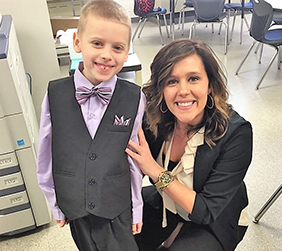 Student dressed in formal attire poses with a teacher