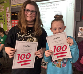 two female students holding an award that say 100