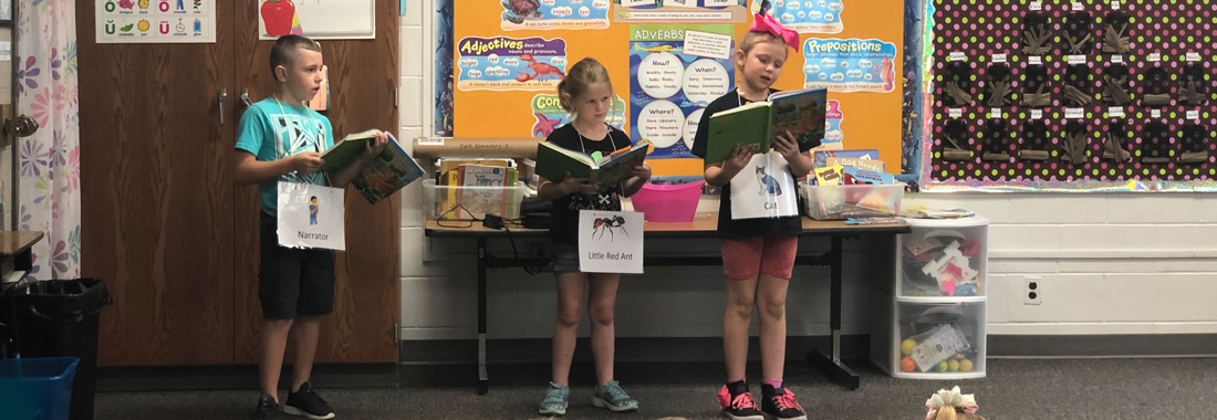 three students reading to the class