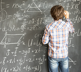 Student writing equations on a blackboard